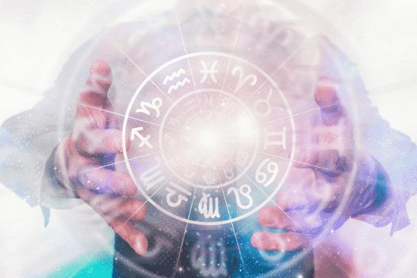 Mãos de homem abertas com horóscopo iluminado e estrelas visto de frente