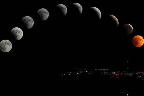 Fases da Lua formando arco em sequência com luzes de cidade ao fundo