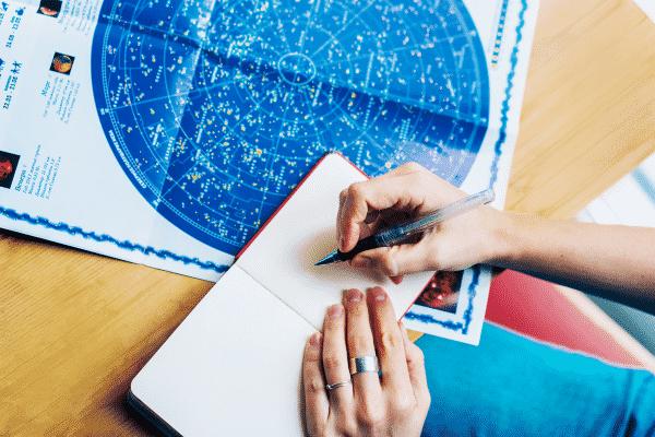 Mãos escrevendo em caderno com mapa astrológico ao fundo