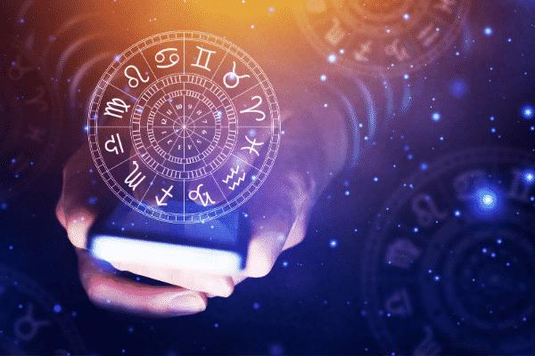 Mãos segurando celular com efeito de horóscopo e estrelas em volta
