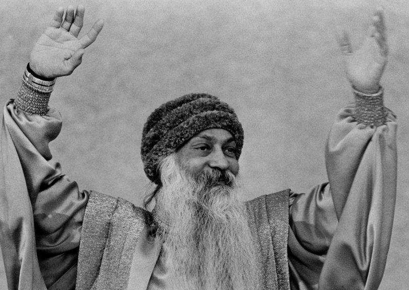 Retrato de Osho com as mãos para o alto, sorrindo