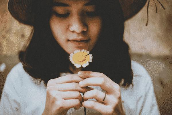 Mulher vista de perto segurando flor próxima ao rosto usando chapéu