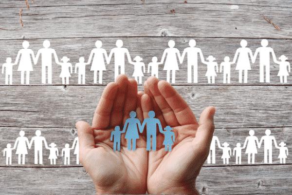 Mão segurando recorte em formato de família com recortes atrás
