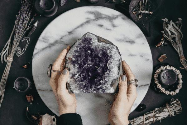 Mãos femininas segurando pedra ametista vista do alto