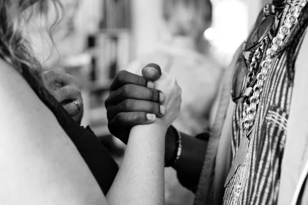 Pessoa negra e pessoa branca dando as mãos.