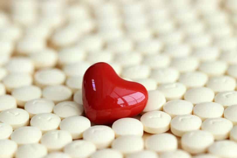 Imagem de várias pílulas contraceptivas na cor branca. Ao centro dela, uma pílula em formato de coração na cor vermelha.