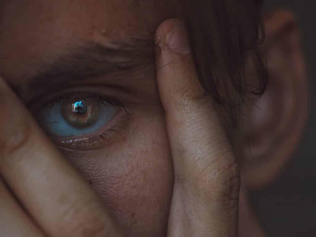 Close no olho verde de um homem branco com a mão ao redor do olho.