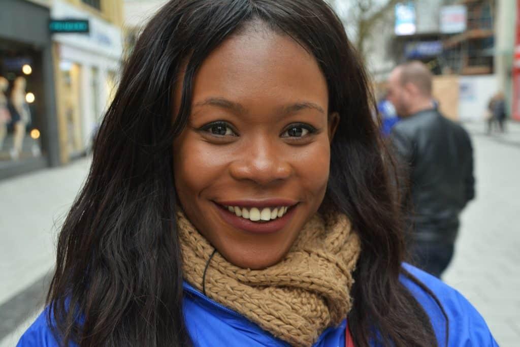 Imagem de uma linda mulher negra com seus cabelos pretos e longos. Ela está sorrindo e usa um cachecol marrom envolta do seu pescoço.