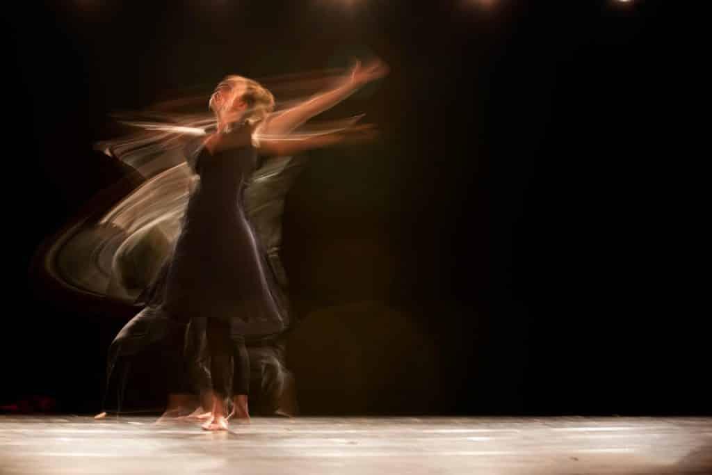 Mulher dançando com os braços abertos sendo contornada pelos reflexos de seus movimentos.