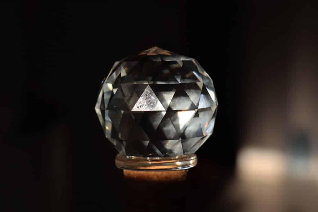 Cristal redondo multifacetado transparente em um fundo preto.