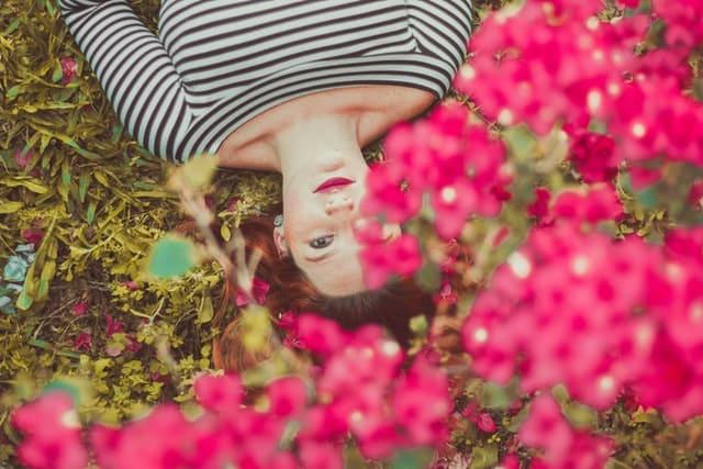 Mulher deitada no chão com flores em frente vista do alto