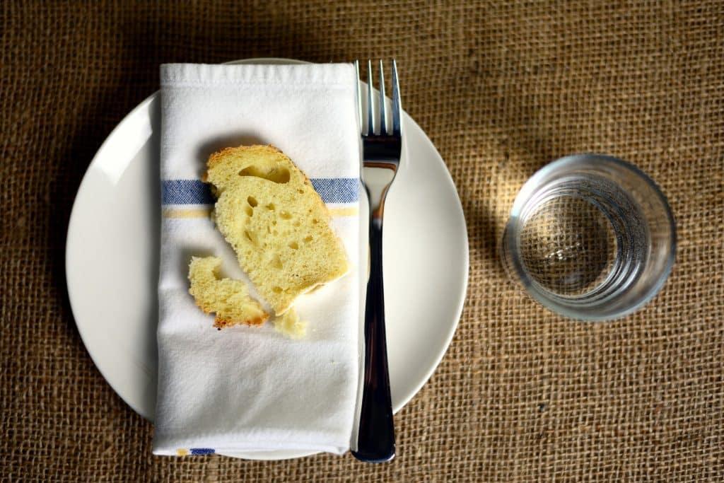 Imagem de uma mesa com uma toaha de juta. Sobre ela um prato branco com um guardanapo de boca sobre ele e um pedaço de pão e um garfo. Ao lado um copo com água.