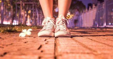 Imagem de um pé calçando um tênis. A pessoa está indo caminhar em uma noite bem gostosa e de muito calor. Ao lado do pés, uma flor branca.