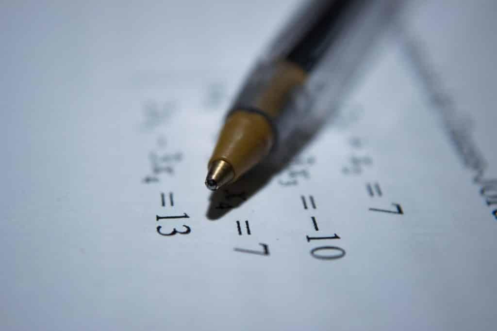 Imagem desfocada de um papel com cálculos e uma caneta em cima.