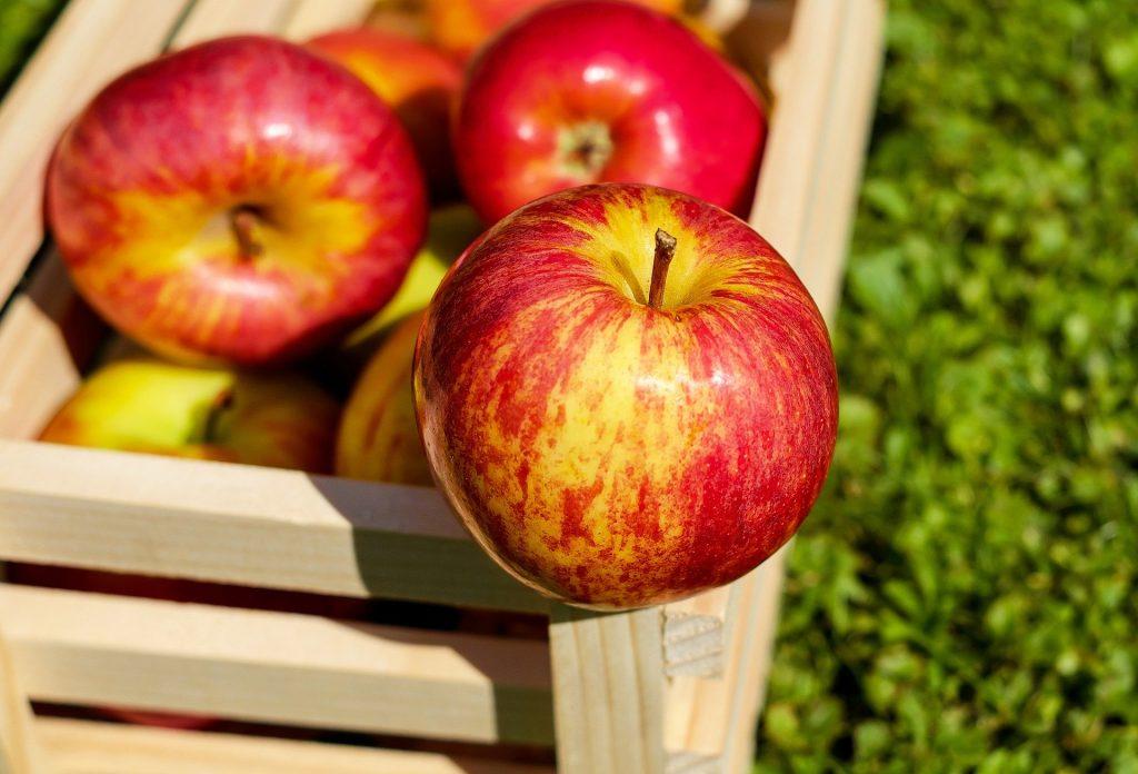 Imagem de um caixote de madeira na cor clara e dentro dele várias maçãs bem vermelhinhas.