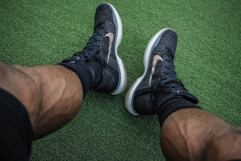 Imagem das pernas musculosas de um atleta masculino. Ele está sentado em um gramado. Usa bermuda, tênis e meia esportiva na cor preta.