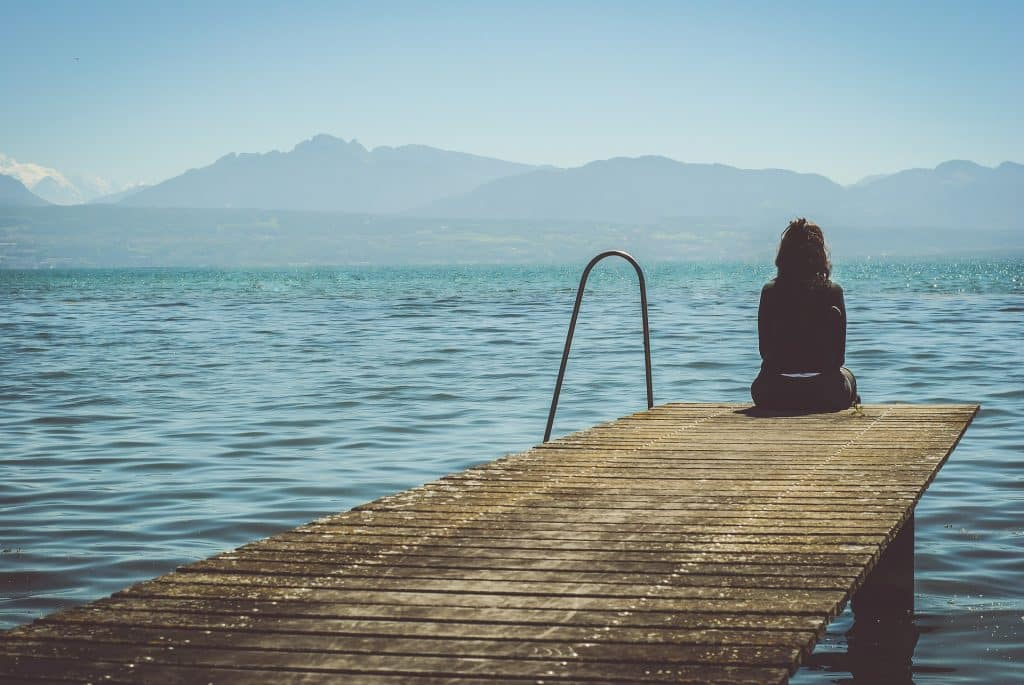 Imagem de uma doca e nela uma mulher solitária está sentada olhando para a imensidão de um lindo mar azul.