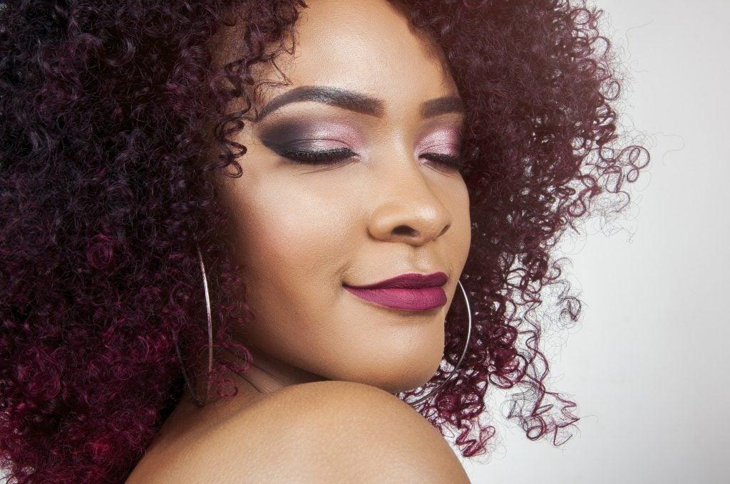 Imagem de uma bela mulher negra de cabelos cacheados na cor vermelho escuro. Ela está com os olhos e a boca pintados e usa um lindo e grande brinco de argolas.