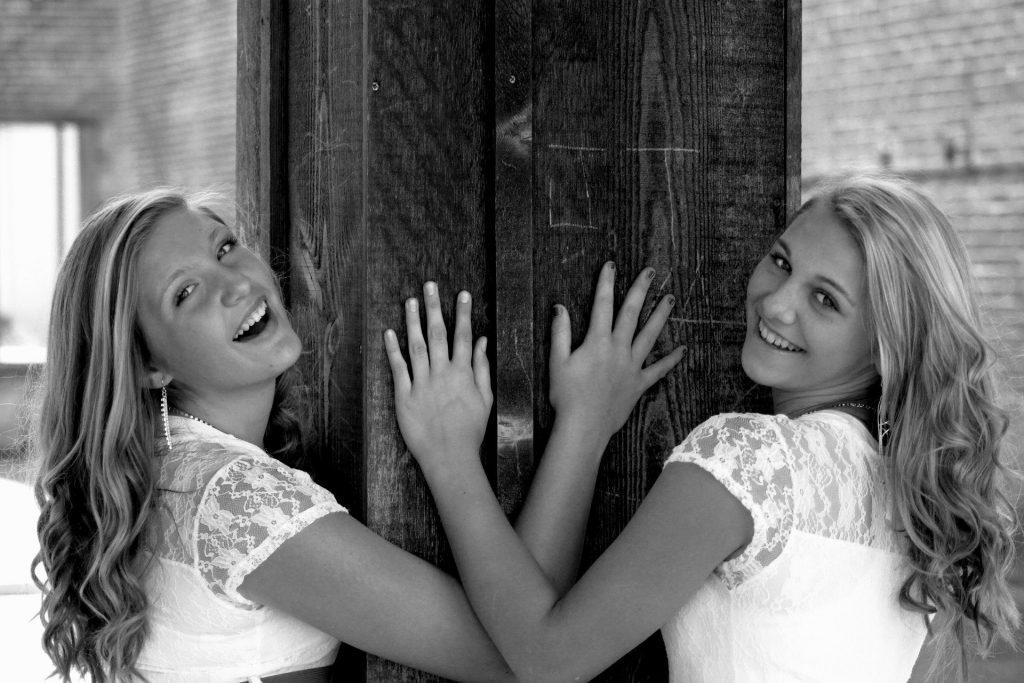 Imagem preto e branco de duas lindas jovens de cabelos brancos sorrindo.