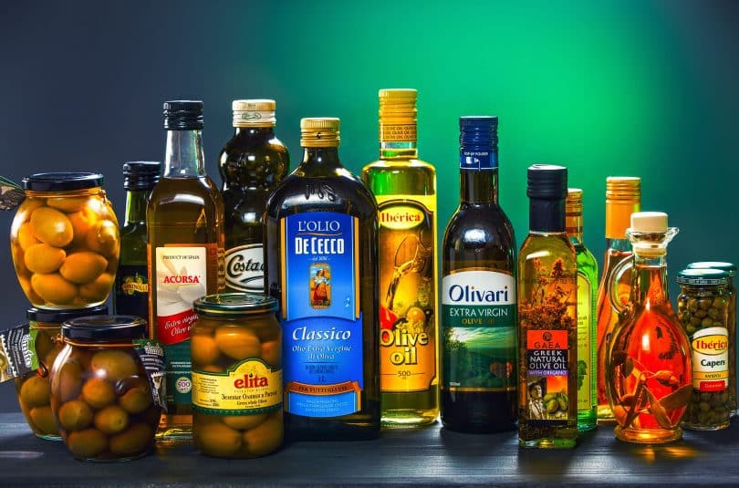 Imagem de várias garrafas de vidro cheias de azeites e outros tipos de óleos vegetais.