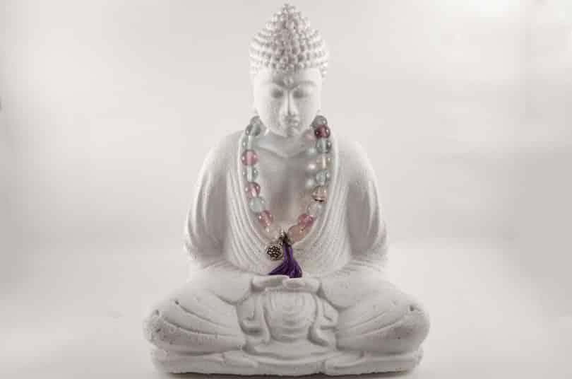 Imagem da estátua de Buddha em posição de meditação. No pescoço dele, uma japamala colorida feita de miçangas.