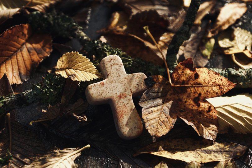 Imagem de um chão repleto de folhas secas e sobre elas uma pequena cruz, simbolizando um retiro espiritual.