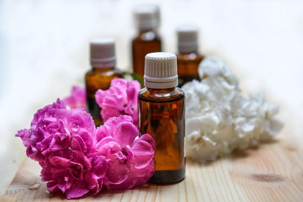 Imagem de óleos essenciais para serem utilizados na aromaterapia. Eles estão sobre uma mesa de madeira e ao lado arranjos de flores na cor rosa e branca complementam a decoração da mesa.