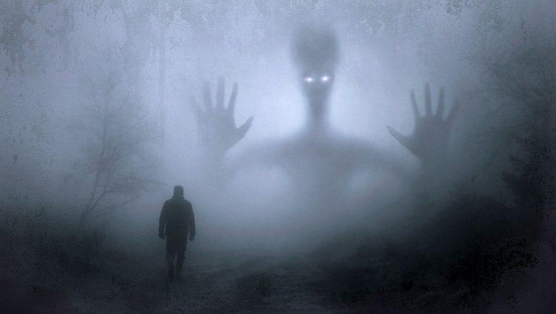 Imagem de um pesadelo refletido em um espírito assombrando uma pessoa em um floresta.