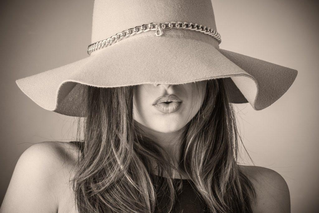 Imagem preto e branco do rosto de uma mulher. Ela está usando um chapéu de feltro grande e que cobre os seus olhos.