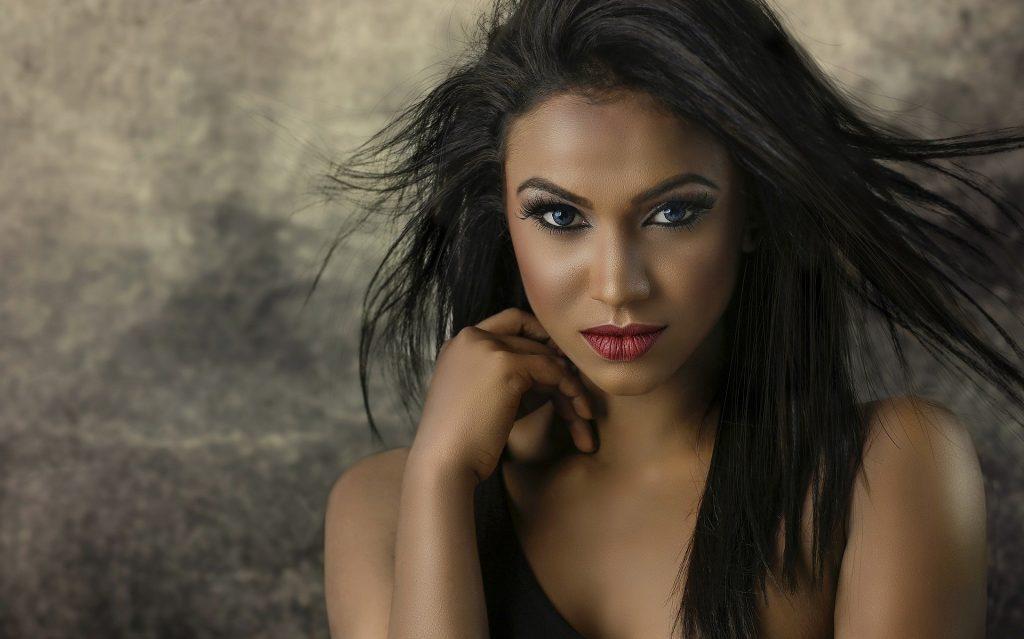 Imagem de uma linda mulher modelo negra, com cabelos longos, olhos, boca pintados.
