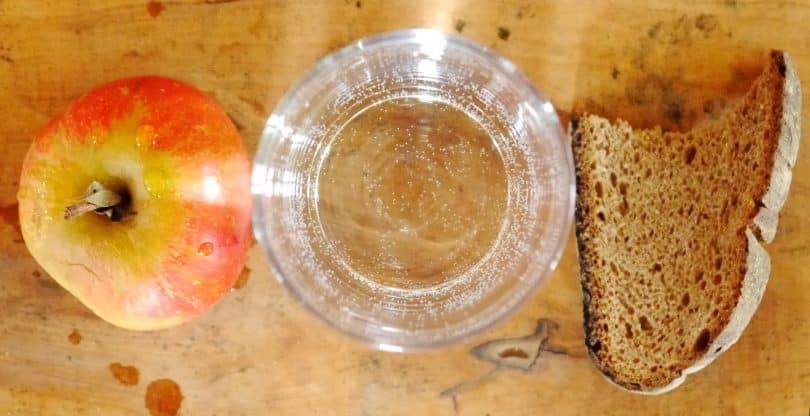 Imagem de uma mesa e sobre ela uma maçã vermelha, um copo com água e uma fatia de pão caseiro, representando o jejum.