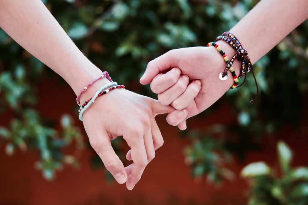 Duas mãos de duas pessoas com os dedos mínimos entrelaçados.