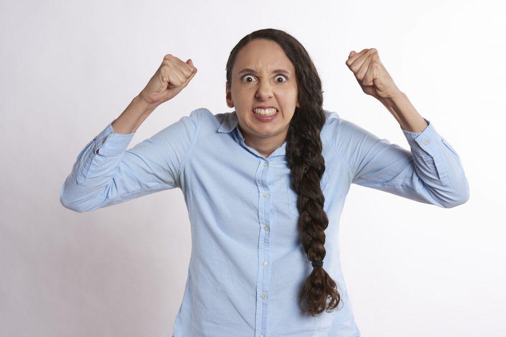 Imagem de uma mulher de mau humor. Ela usa uma camisa azul clara e uma trança longa em seu cabelo.