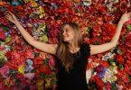 Imagem de fundo de flores coloridas e sobre ela uma jovem deitada. Ela usa um vestido preto e cabelos longos e loiros.