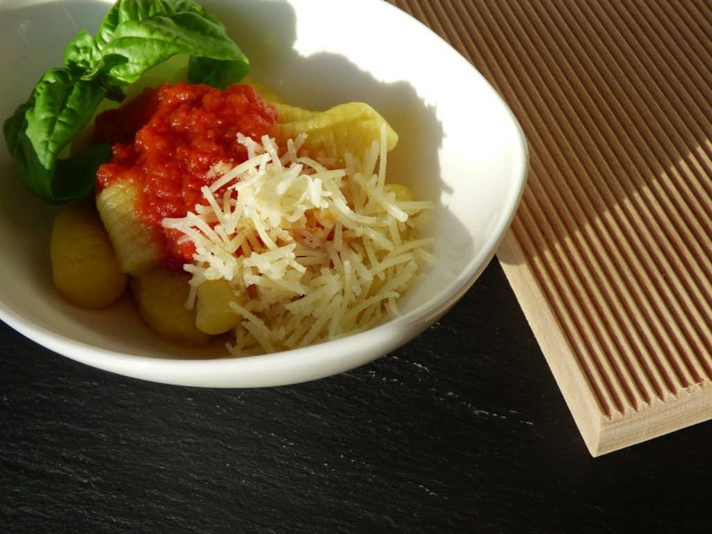 Prato branco com nhoque, molho vermelho, uma folha verde e queijo ralado.