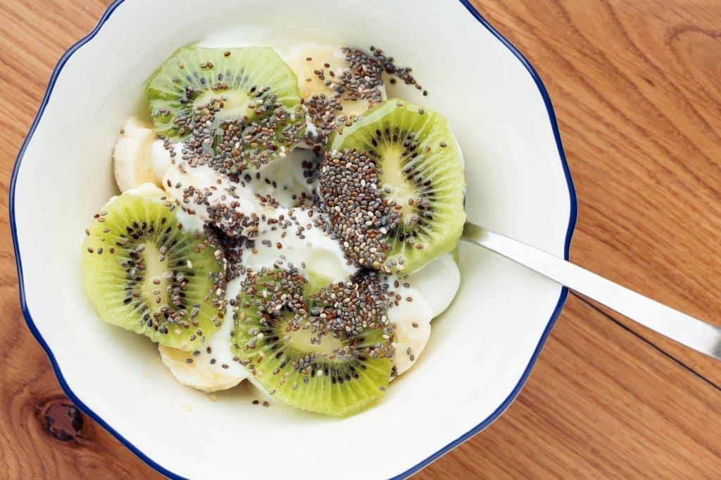 Imagem de uma tigela branca com kiwi, banana, iorgute e semestes de chia.