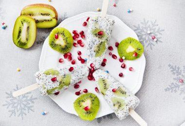 Imagem de três picolés feitos de semente de chia dispostos sobre um prato branco de porcelana decorado com kiwis fatiados.
