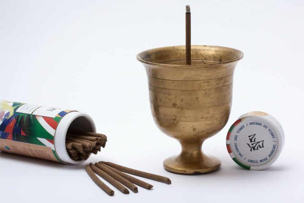 Imagem de um caixa com incenso de palo santo, uma taça de bronze com um incenso dentro sendo queimado.