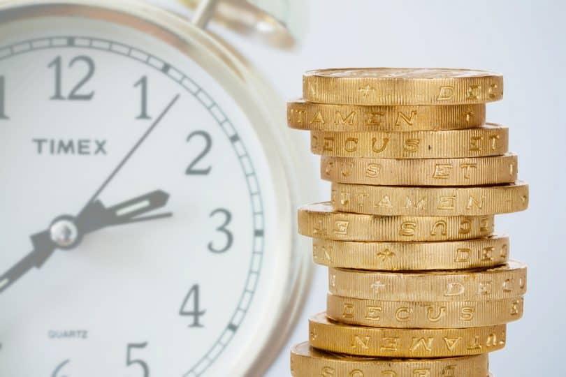 Imagem de um relógio de fundo branco e aro dourado e ao lado dele um monte de moedas douradas.