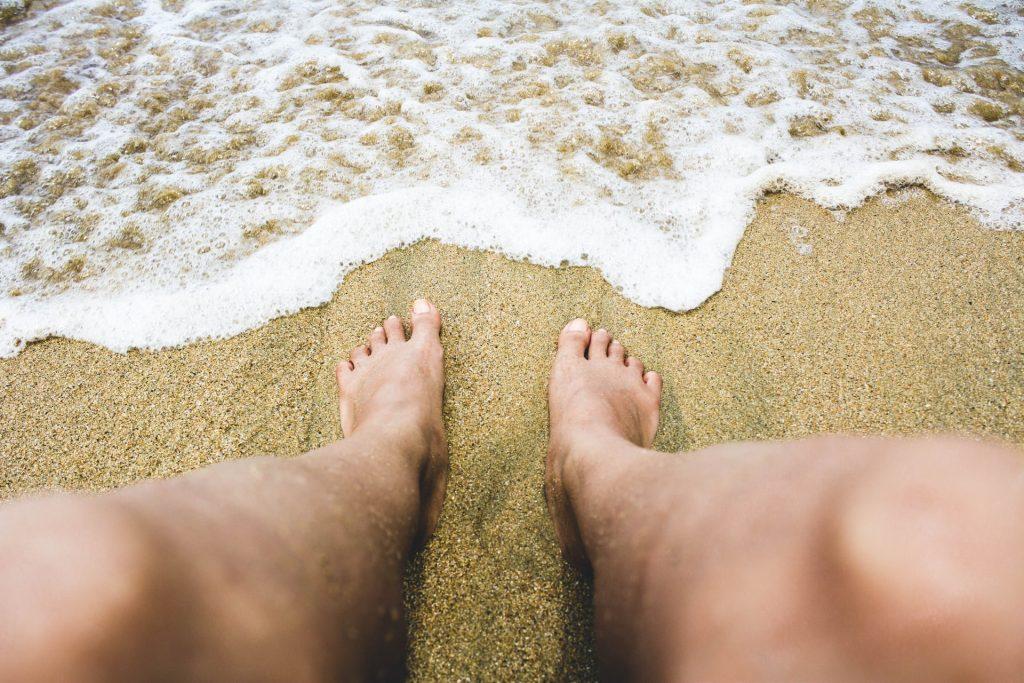 Pés brancos masculinos na areia da praia e onda à frente.