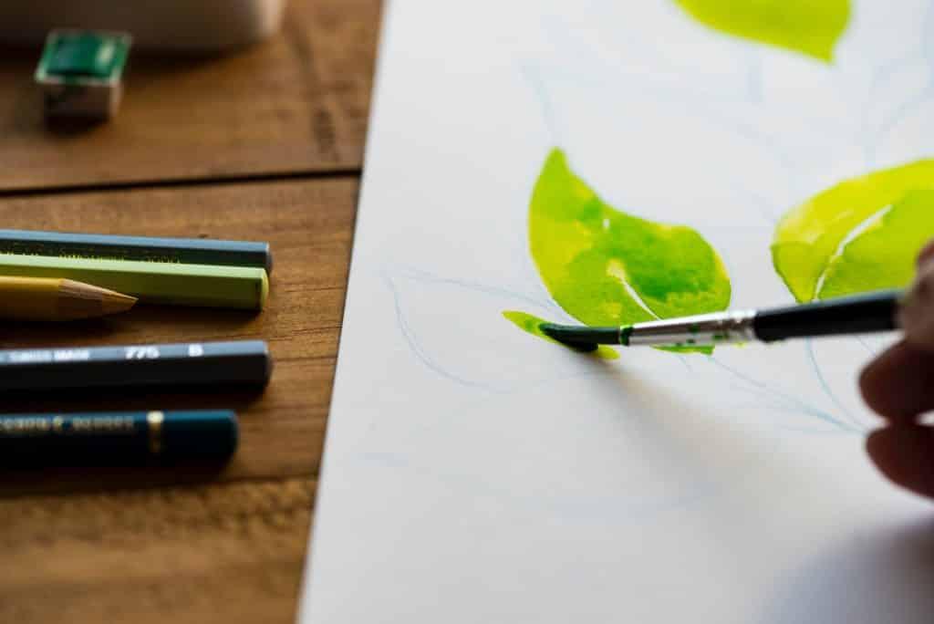 Pessoa pintando folhas de árvore em um papel com tinta aquarela.