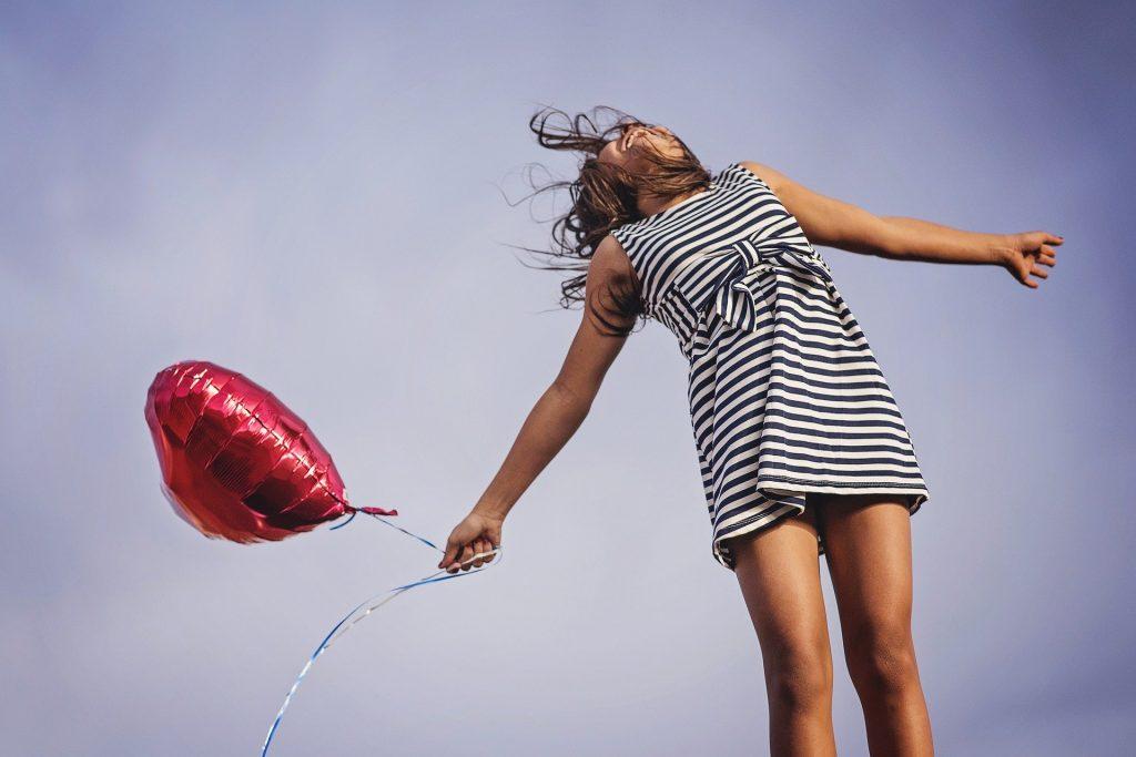 Mulher de braços abertos em um fundo de céu segurando um balão vermelho de coração.