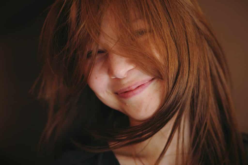 Mulher branca de cabelos ruivos no rosto com expressão calma