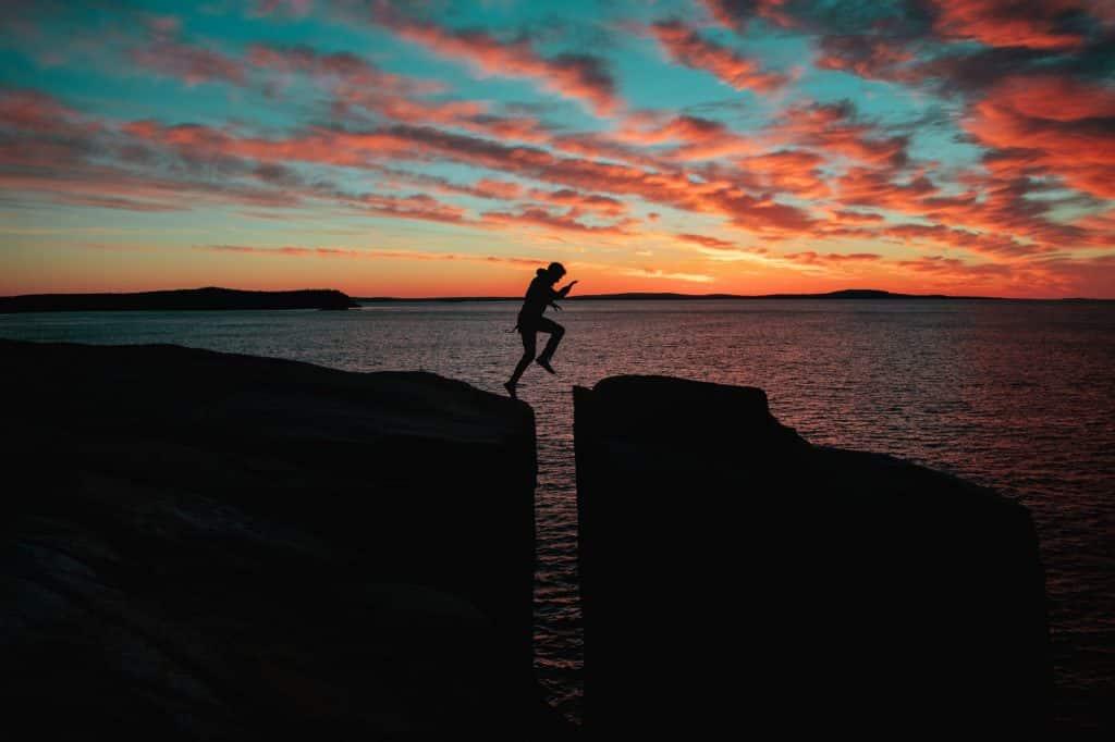 Homem pulando entre pedras durante o pôr-do-sol.