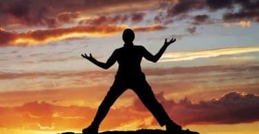 Silhueta masculina com braços e pernas abertas com pôr-do-sol ao fundo.