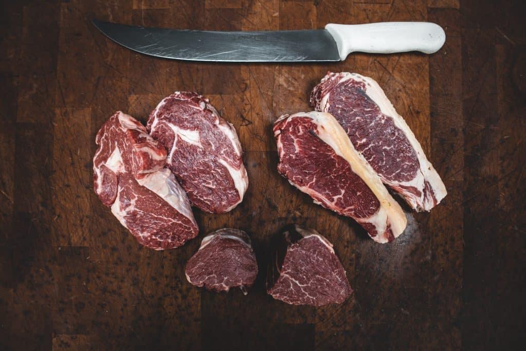 Fatias de carne bovina em cima de uma tábua de madeira.