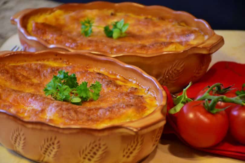 Imagem de duas travessas com lasanhas vegetarianas prontas para serem servidas. Ao lado das travessas dois tomates bem vermelhinhos.