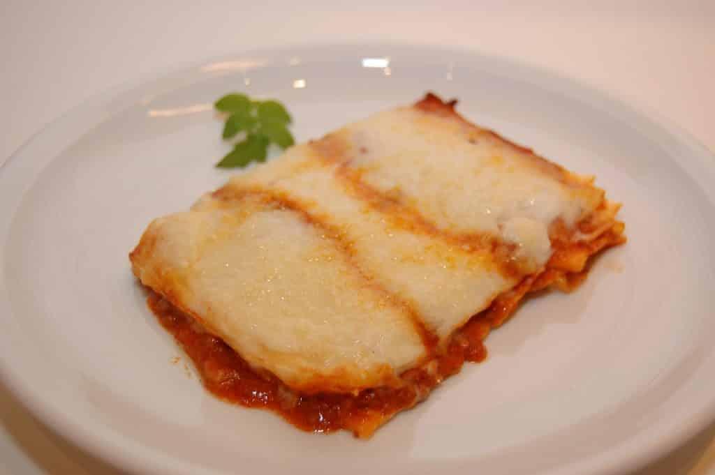 Imagem de um prato redondo de porcelana branco e sobre ele um pedaço de lasanha de berinjela coberto com queijo.