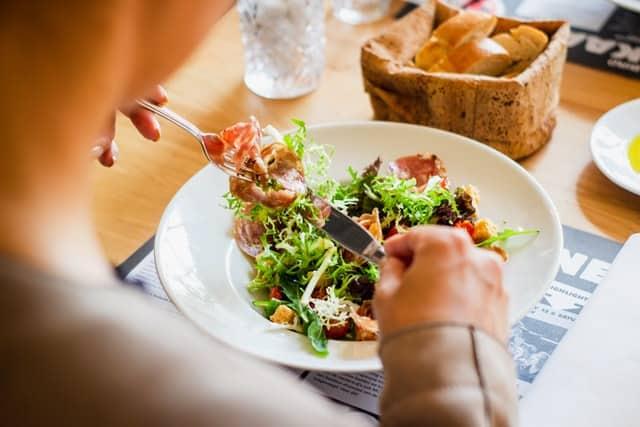 Homem almoçando prato com salada e comida saudável