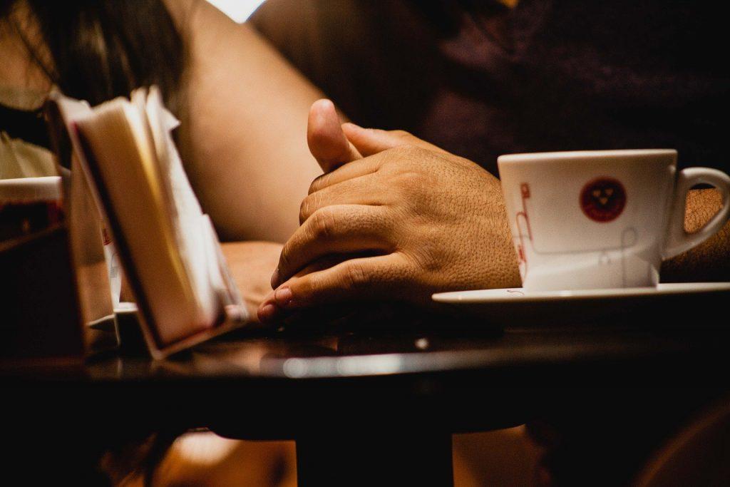 Imagem de um casal sentados em uma cafeteria. O homem segura uma das mãos da mulher. É uma demonstração de carinho e afeto.